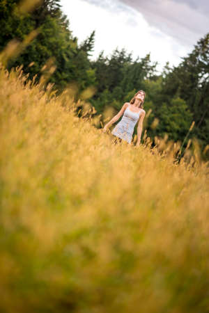 Young woman standing in an autumn meadow looking up in the sky smiling as she enjoys the beauty of nature and simplicity of life.