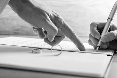 firmando: Imagen monocromática de la mano apuntando macho a una mujer en firmar los papeles del divorcio legal o registro de matrimonio con anillos de boda en el documento. Foto de archivo