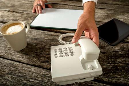 Business persona con carta in bianco e tazza di caffè fresco di fronte a lui circa a fare una telefonata in un supporto clienti e il concetto di telemarketing. Archivio Fotografico - 45947881