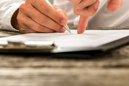 financial agreement: Closeup of male hand pointing where to sign a contract, legal papers or application form.