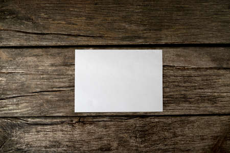 message text: Top view of blank white peace of paper ready for your message, text or product on textured wooden background. Stock Photo