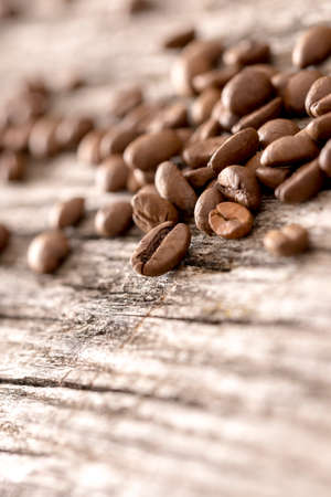 coffee beans: Coffee beans sprinkled on a textured rustic wooden boards with copy space ready for your text or message. Stock Photo