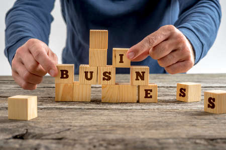 Primo piano delle mani di un uomo che, costruendo la parola d'affari con blocchi di legno su un tavolo rustico in una immagine concettuale.