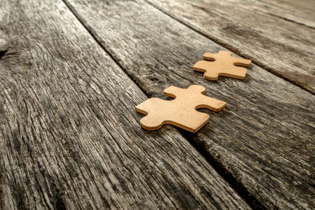two visions: Two puzzle pieces lying on wooden rustic boards. Conceptual of innovation, solution finding and integration.