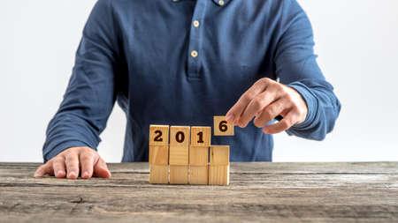 decide: Vista frontal de un hombre montaje de un signo 2016 con cubos de madera mientras planea su futuro y decide sobre su resoluci�n de a�o nuevo.