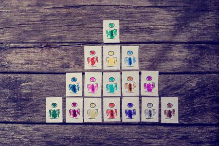 Liderazgo, recursos humanos y gestión de equipos de concepto con una serie de cartas a mano que representan las personas estructuradas en una pirámide sobre tablas de madera rústicos.