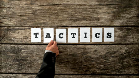 officer: Overhead view of strategic business partner assembling the word tactics with white cards over rustic wooden background.