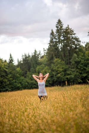 loosen up: Young woman standing in an autumn field with high grass holding her hands behind her head looking up in the sky enjoying a serene moment. Stock Photo