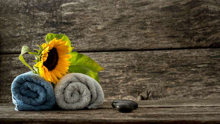 Spa setting for a couple - two rolled towels with beautiful blooming sunflower on top and two black spa stones lying on textured rustic wooden ambient. Banque d'images