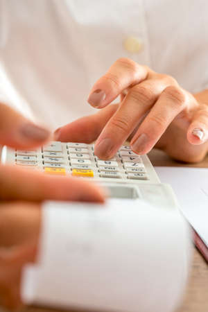Front view of female accountant calculating with adding machine and checking a receipt. Closeup of her hands.