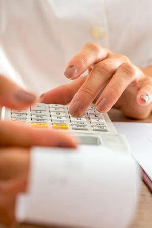 Vue de face d'un comptable féminin calculant en ajoutant une machine et en vérifiant un reçu. Gros plan de ses mains. Banque d'images - 46493064