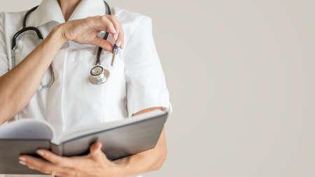 bata blanca: Vista frontal de mujer médico con estetoscopio alrededor de su cuello a punto de tomar una pluma de un bolsillo de su chaqueta médica blanco para hacer una nota u observación en un cuaderno.