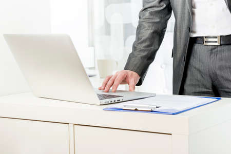 navigating: Businessman standing using a laptop placed on a white cabinet with a clipboard alongside, close up of his hand navigating the internet.
