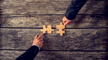 Retro style image of two business partners each placing one matching piece of puzzle on a textured wooden table. Conceptual of cooperation, innovation and success. Stock Photo