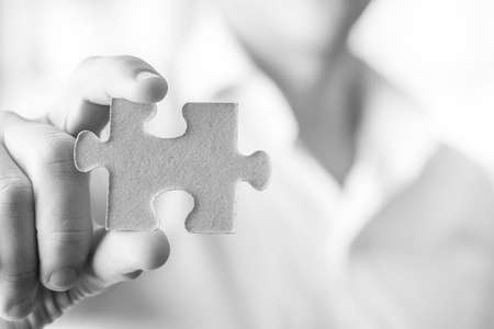 Black and white image of businessman or innovator holding a blank puzzle piece towards you, with copy space ready for your idea, text or sign. Stock Photo