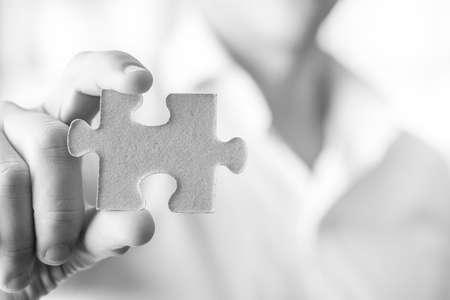 piezas de rompecabezas: Imagen blanco y negro de hombre de negocios o innovador sosteniendo una pieza del rompecabezas en blanco hacia usted, con copia espacio listo para su idea, texto o signo.