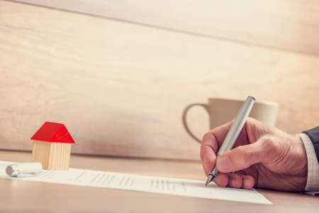 Primo piano di documenti di assicurazione firma mano maschi, contratto di vendita o di casa ipoteca documenti con penna stilografica, casa giocattolo di legno che si siede sul lavoro di ufficio. Archivio Fotografico