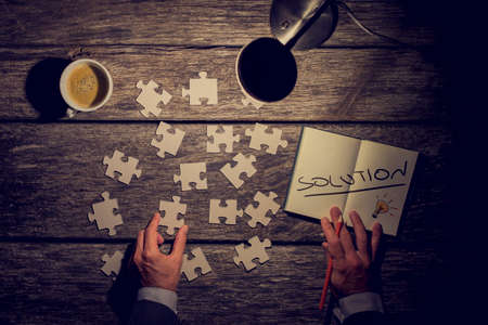 Retro image of a businessman, innovator or student looking for solution to his challenge or problem while metaphorically rearranging puzzle pieces and taking notes on his rustic wooden work desk and his table lamp turned on. Archivio Fotografico