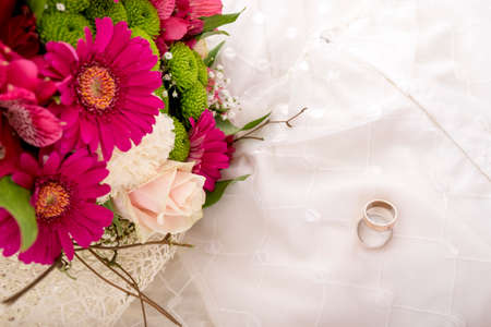 Wedding setting - top view of bride and groom rings and beautiful colourful bouquet of flowers on white wedding gown.