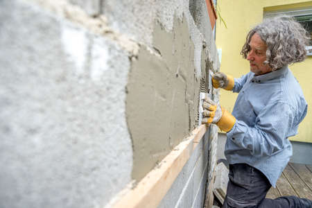 renovating: Builder applying tiles to a wall with tile cement in an architectural, renovation, DIY or new build concept, oblique angle perspective.