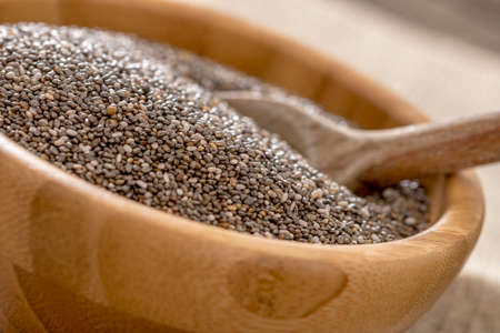 heaping: Closeup of heaping wooden bowl of healthy nutritious Chia seeds. Stock Photo