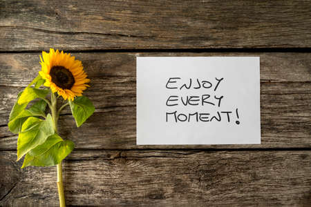 fulfilled: White card with an Enjoy every moment message lying next to a beautiful blooming sunflower on a textured wooden desk in order to encourage you to seize the moment and live a fulfilled life. Stock Photo