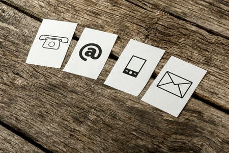 mobile telephone: Contact and communication icons, telephone, at sign, mobile and mail, on four white cards spread over textured rustic wooden boards.