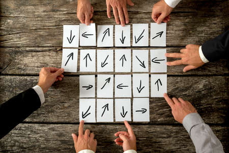 argumentation: Meeting of business partners each holding a card with arrow representing his idea about how to lead an organization or company and which way and strategies to undertake in order to achieve success.