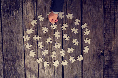 Man choosing a puzzle piece from a neatly arranged circle of pieces on a rustic wooden floor in a concept of problem solving and solutions, vintage effect toned image.