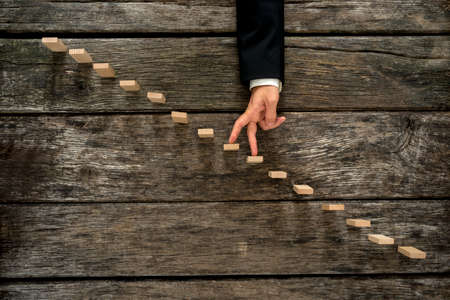 moving forward: Businessman walking his fingers up wooden steps or pegs resembling a staircase mounted in rustic wooden boards in a conceptual image of success, promotion and advancement.