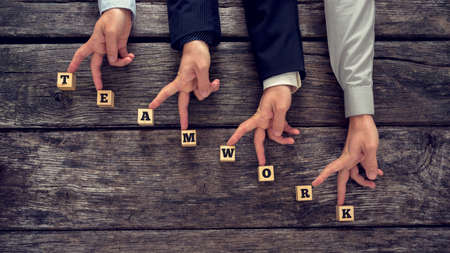 business education: Teamwork concept with the word spelt out on wooden blocks in the form of a staircase with businessmen walking their fingers up the steps of success.