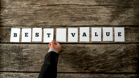 values: Salesman assembling a Best value sign with white cards over a textured rustic wooden desk. Stock Photo