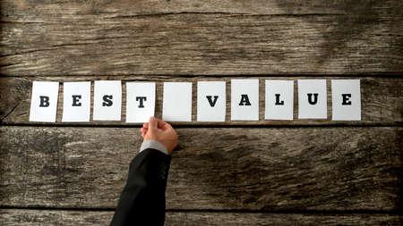 valor: Vendedor montaje de una señal mejor valor con tarjetas blancas sobre un escritorio de madera rústica con textura.