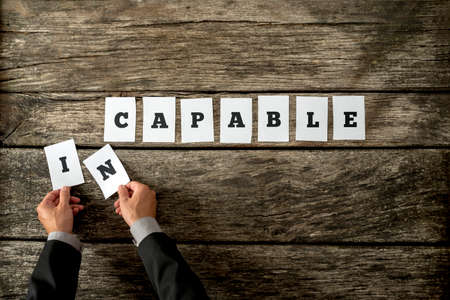 capable: Overhead view of personal motivator or consultant removing letters IN from the word Incapable changing it into Capable. Concept of personal transformation and belief in ones abilities and potential.