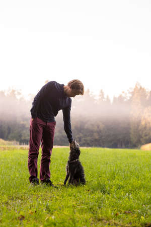 pat down: Young man standing enjoying nature as he  bends down to his black dog to pat it.