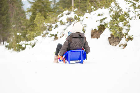 toboggan: View from behind of a mother sitting in a toboggan with her child going downhill in a snowy winter forest.