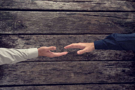 agreement: Overhead view of two businessman about to shake hands in congratulation, agreement or greeting over a rustic textured wooden surface, with a retro effect.