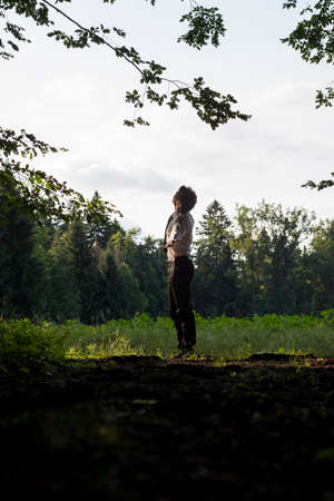 standing up: Young man enjoying nature standing with outstretched arms looking up into the sky in a rural field, side view.