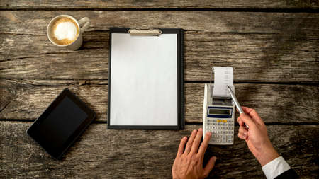 bookkeeping: Business accountant or financial adviser checking income and expenses in order to write an annual report as he makes calculations on adding machine. With blank sheet of paper in front of him.