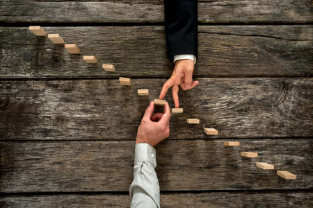 achievement concept: Conceptual image of business partnership and support - businessman supporting wooden step in a staircase made of pegs as his partner walks his fingers up towards growth, achievement and development.