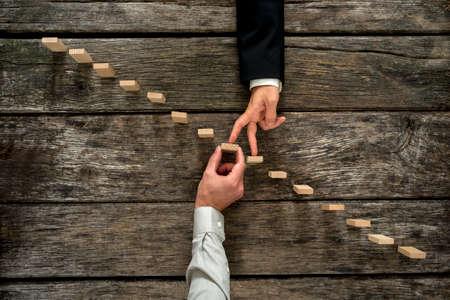 Konzeptionelle Bild der Business-Partnerschaft und Unterstützung - Geschäftsmann tragenden Holz Stufe einer Treppe von Zapfen gebildet, wie sein Partner Spaziergänge mit den Fingern bis auf Wachstum, Leistung und Entwicklung.