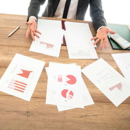 auditoría: Asesor financiero ocupado trabajando en su escritorio de negocios con muchos documentos, gráficos e informes puso todo sobre la mesa, que muestra un gesto dudoso con las manos. Foto de archivo