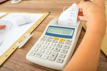 billing: Tax and accounting concept - female accountant calculating costs and expenses using adding machine checking the receipt and comparing it to paperwork and data.