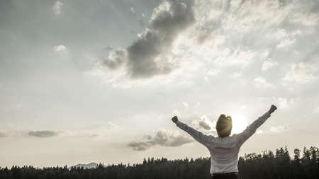 Desaturated obraz z vítězství, moc a úspěch - podnikatel stojí s rukama dosahující až k nebi se jeho ruka dělat pěsti, jak se slaví své osobní a obchodní úspěch.