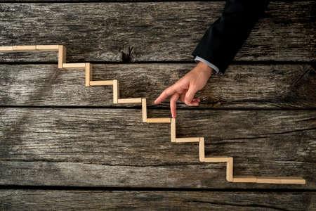 사업가 또는 학생 개인 및 경력 개발, 성공과 열망의 개념적 이미지에 소박한 나무 보드에 장착 된 계단을 닮은 나무 단계까지 자신의 손가락을 산책. 스톡 콘텐츠