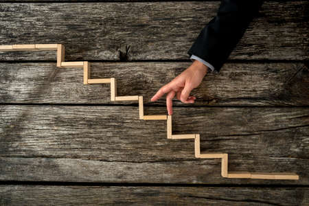 advancement: Businessman or student walking his fingers up wooden steps resembling a staircase mounted in rustic wooden boards in a conceptual image of personal and career development, success and aspiration.