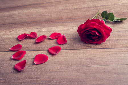 romance rose: Romantic red rose and heart formed of loose petals lying on a wooden table symbolic of love, romance, Valentines Day and an anniversary, with a retro filter effect.