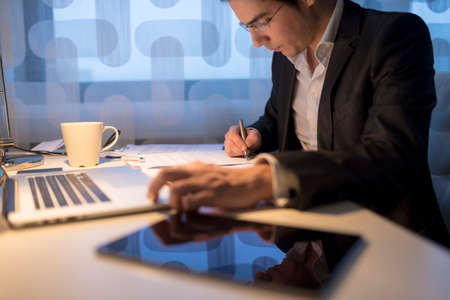 ejecutiva en oficina: El hombre de negocios o un abogado, trabajando horas hábiles finales con ordenador portátil, tableta digital y el café en su escritorio de la oficina mientras se completa su trabajo con la firma de un documento final, se centran en la pluma.