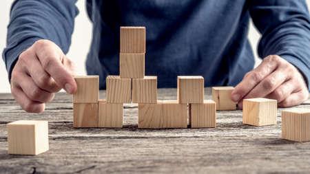 pensamiento estrategico: El hombre en camisa azul ordenar bloques de madera en la mesa rústica en una imagen conceptual. Foto de archivo