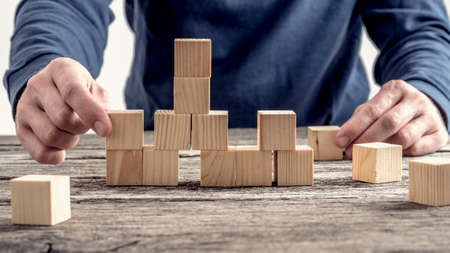 Man in blauw shirt het regelen van houten blokken op rustieke tafel in een conceptueel beeld.